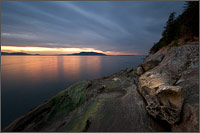 sunset over lummi island with some sandstone tafoni at clayton beach in larrabee state park