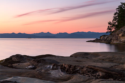 sunset over the coast mountain range and nanaimo harbour from biggs park at duke point in nanaimo british columbia