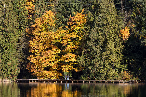 two hikers view fall maple leaves at sasamat lake