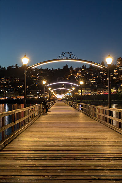 view from end of white rock pier looking back towards city at night
