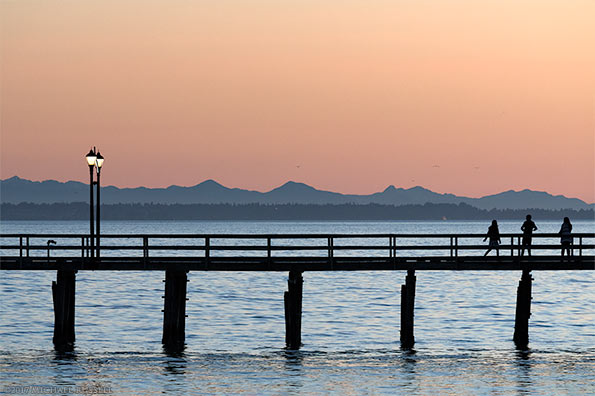 people watching the sunset from white rock pier