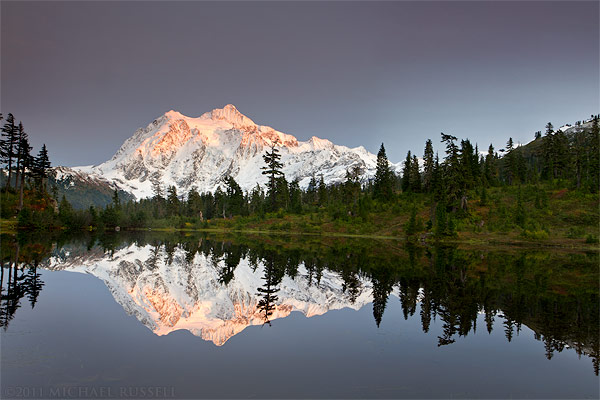 reflection of mount shuksan in the silhouette of picture lake