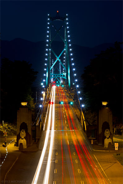 traffic on the lions gate bridge at night from stanley park, vancouver
