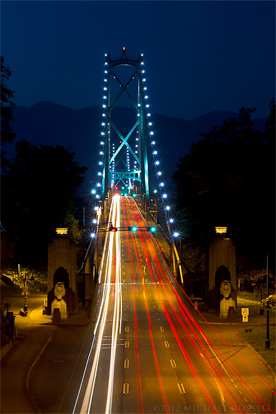 lions gate bridge at night with traffic