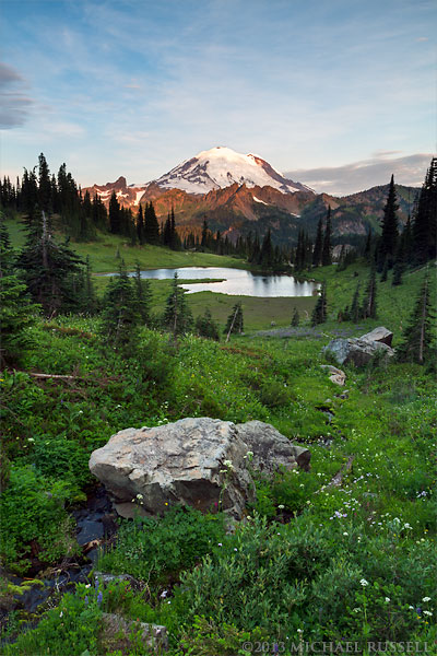 Early morning sun lights up Mount Rainier from above Upper Tipsoo Lake