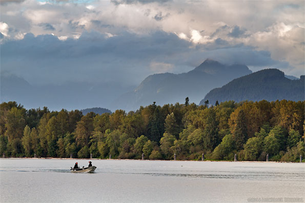 two salmon fishermen in a boat on the fraser river in british columbia