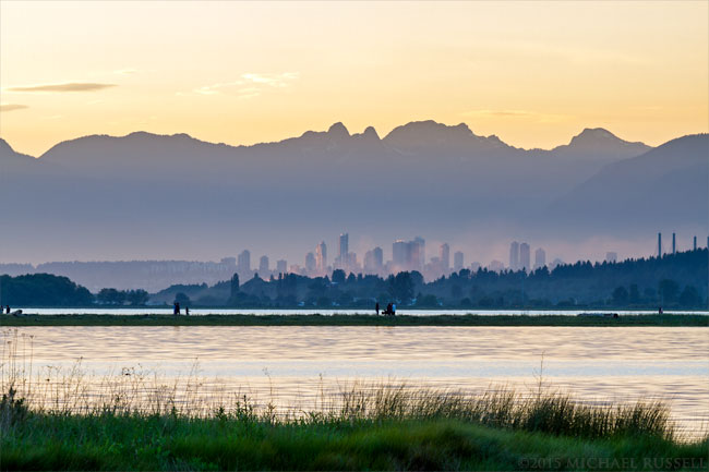 buildings of burnaby and pacific coast range mountains from blackie spit