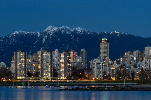 vancouver condo towers and mount seymour blue hour from kits beach