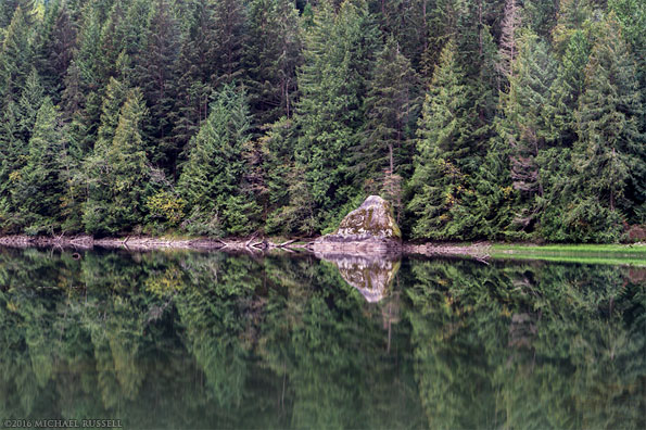 large rock and forest reflected in silver lake