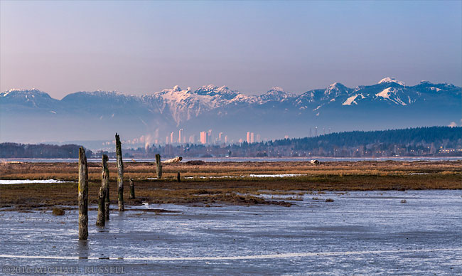 view of burnaby and northshore mountains from crescent beach