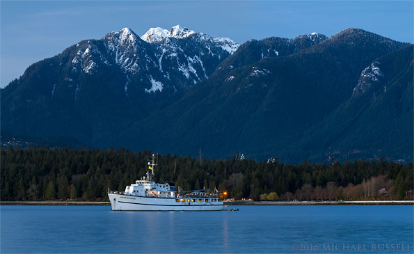english bay view of northshore mountains and the edgewater fortune charter yacht